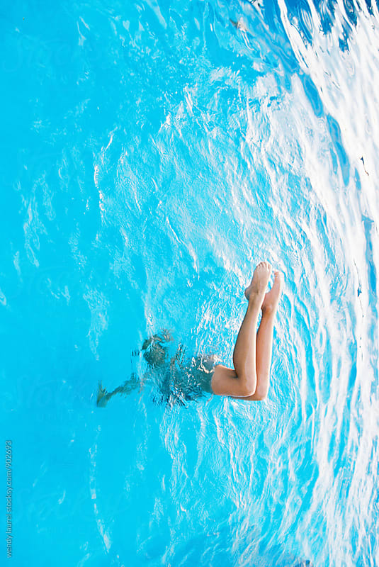 teen doing handstand with bent legs in swimming pool by wendy laurel for Stocksy United