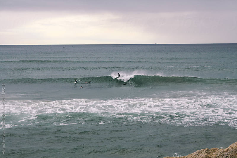 Waves and surfers on the sea by Alejandro Moreno de Carlos for Stocksy United