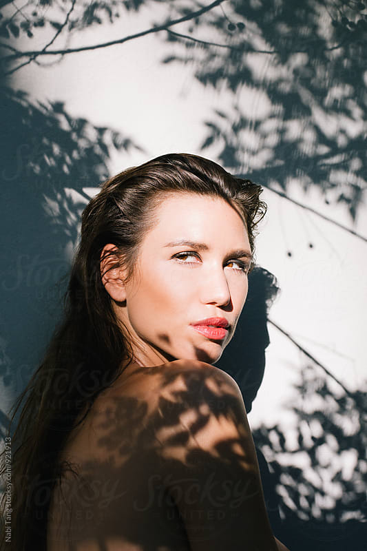 Beautiful sensual young woman under the tree shade in summer sunlight by Nabi Tang for Stocksy United
