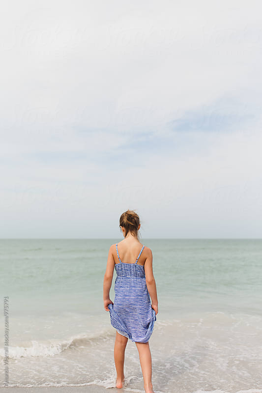 Preteen girl standing at the edge of the water looking out into ocean by Amanda Worrall for Stocksy United