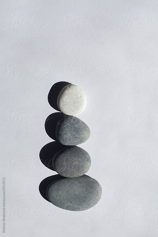 Stones stacked up against a white background. by Shikhar Bhattarai for Stocksy United