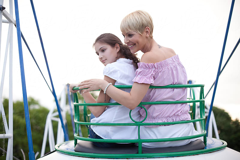 Mother and daughter in amusement park. by Mosuno for Stocksy United
