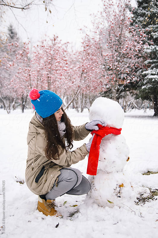 Young woman dressing a snowman by T-REX & Flower for Stocksy United