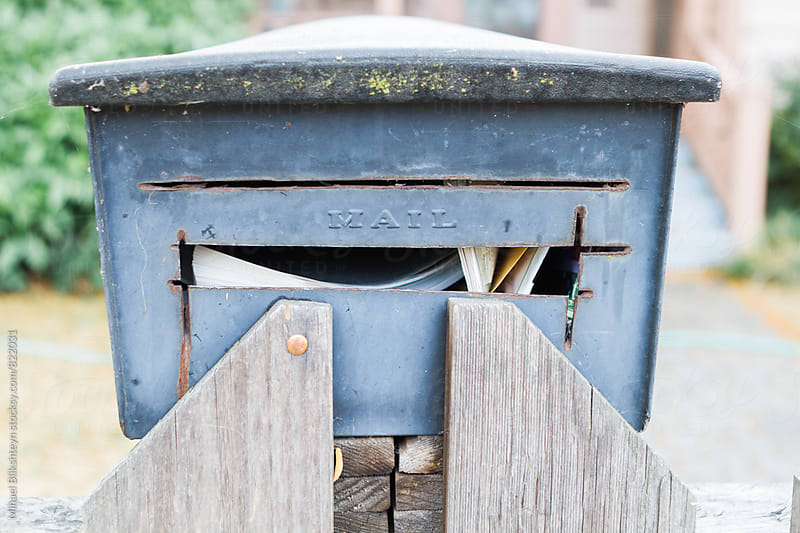 Front view of a blue mailbox with mail in it attached to the fence of a house by Mihael Blikshteyn for Stocksy United