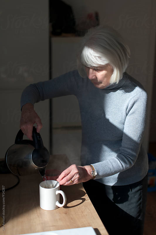 senior woman making a hot drink by Lee Avison for Stocksy United