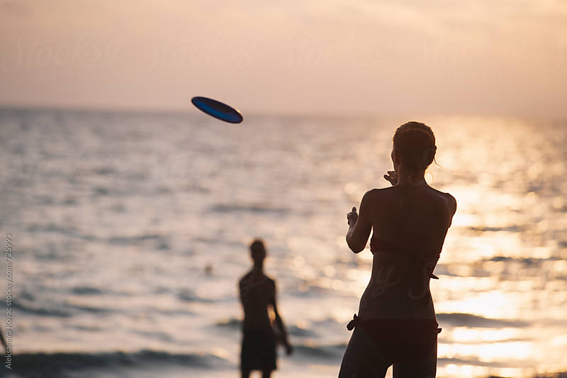 Friends on the beach playing frisbee by Aleksandra Kovac for Stocksy United