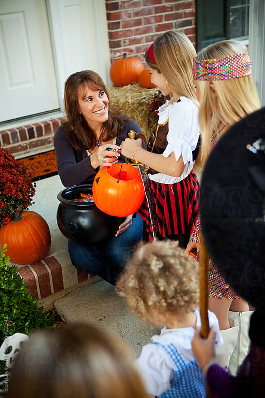 Halloween: Parent Starts Handing Out Halloween Candy by Sean Locke for Stocksy United