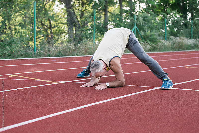 Middle-aged Man Stretching on the Racetrack by Aleksandra Jankovic for Stocksy United