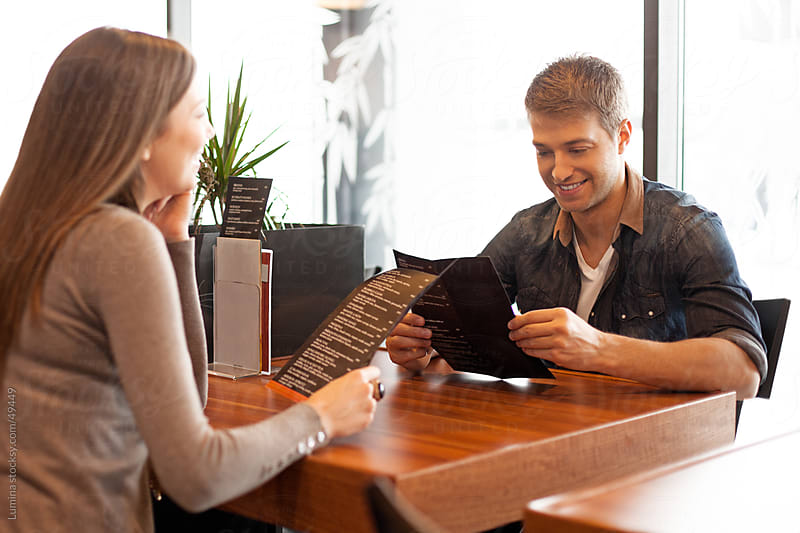 Couple Reading the Menu by Lumina for Stocksy United