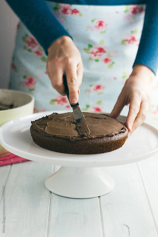 Woman spreading chocolate buttercream onto cake by Kirsty Begg for Stocksy United
