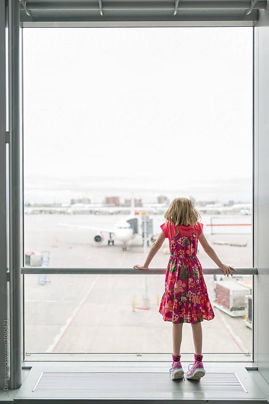 Little Girl Looking Out Window While Waiting For Flight at Modern Airport Traveller Lounge by JP Danko for Stocksy United