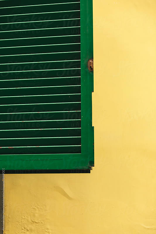 Green window cover against yellow wall by Aleksandar Novoselski for Stocksy United