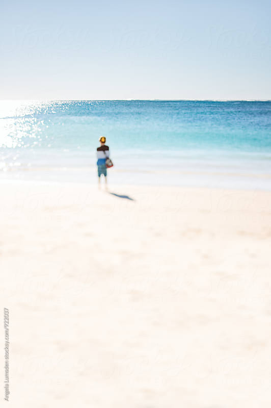 Boy with duffel bag walking along a beach on a sunny afternoon by Angela Lumsden for Stocksy United