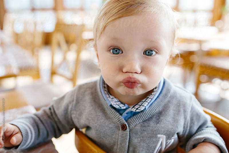 Baby pulling a cute face at the camera by Amir Kaljikovic for Stocksy United