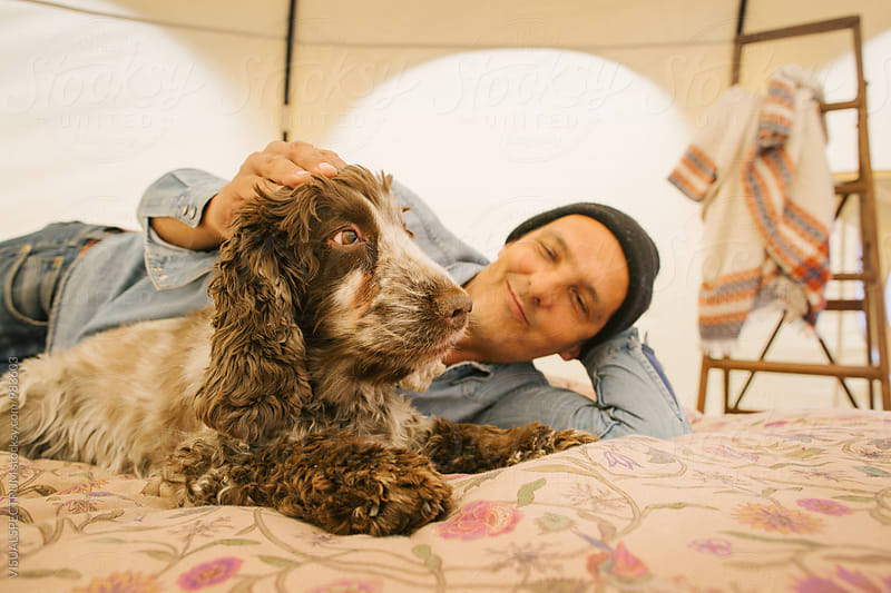 Caucasian Man Stroking Cocker Spaniel on Bed Inside Large Circular Tent by VISUALSPECTRUM for Stocksy United