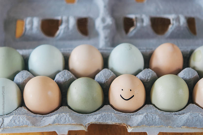 a carton of organic eggs, one with a smiley face by Deirdre Malfatto for Stocksy United
