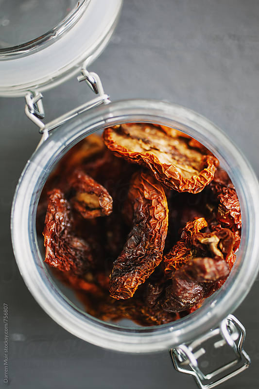 Sun dried tomatoes: Closeup of an open jar of sundried tomatoes. by Darren Muir for Stocksy United
