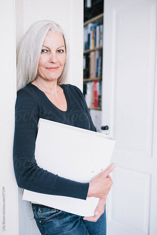 Senior woman standing a door case, holding a folder. by Lilly Bloom for Stocksy United
