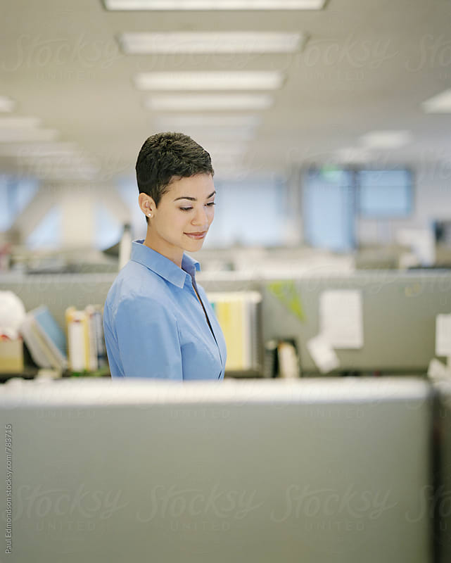 Female office worker, standing in cubicle by Paul Edmondson for Stocksy United