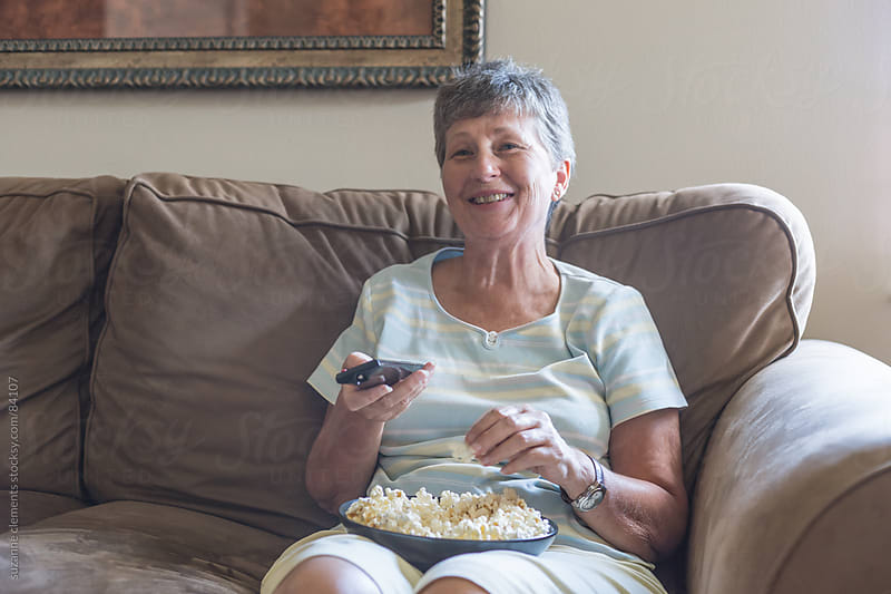 Woman Watches TV at Home on the Couch by suzanne clements for Stocksy United