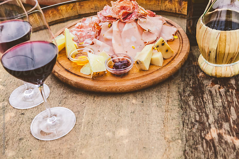 Rustic Chopping Board with Sliced Salami, Tuscan Cheese and two Glasses of Wine by Giorgio Magini for Stocksy United