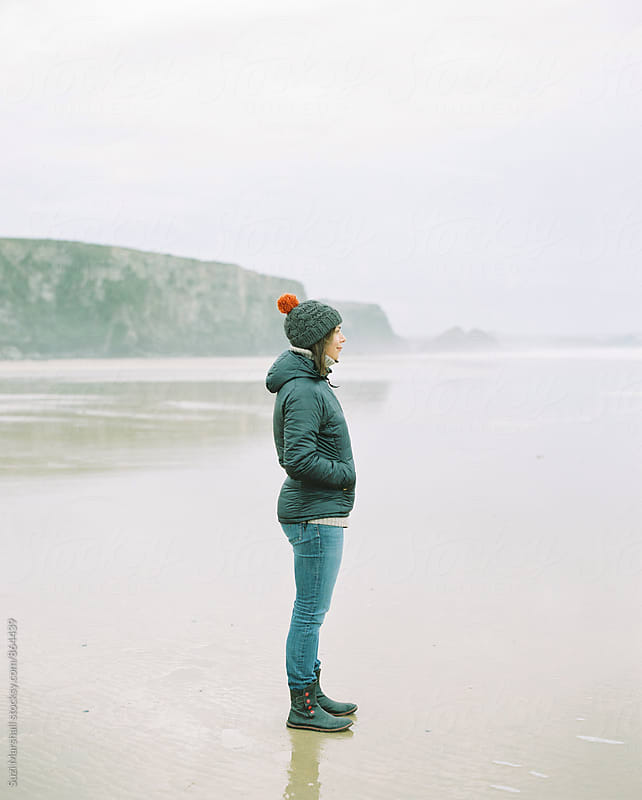 Woman standing on a beach on a foggy winter day looking out to sea by Suzi Marshall for Stocksy United