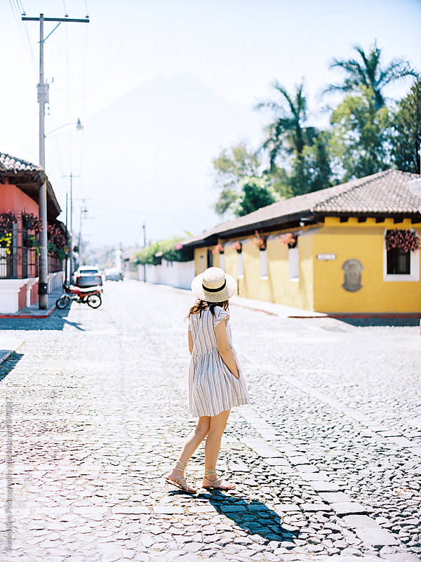 Woman walking on cobblestone street by Daniel Kim Photography for Stocksy United