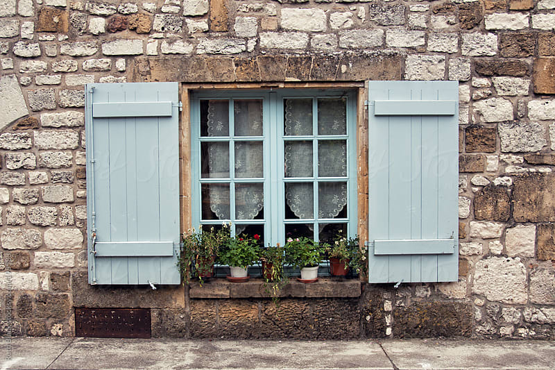 Mediterranean window with wooden shutters and flower pots by Ruth Black for Stocksy United