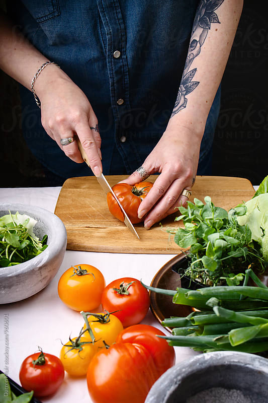 Woman slicing tomato on a wooden cutting board. by Darren Muir for Stocksy United