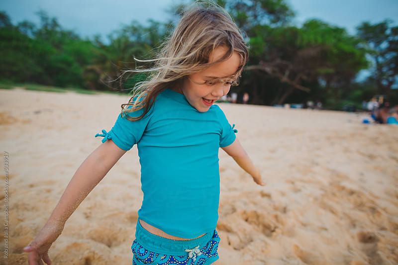 Cute young girl playing in wind on tropical beach by Rob and Julia Campbell for Stocksy United