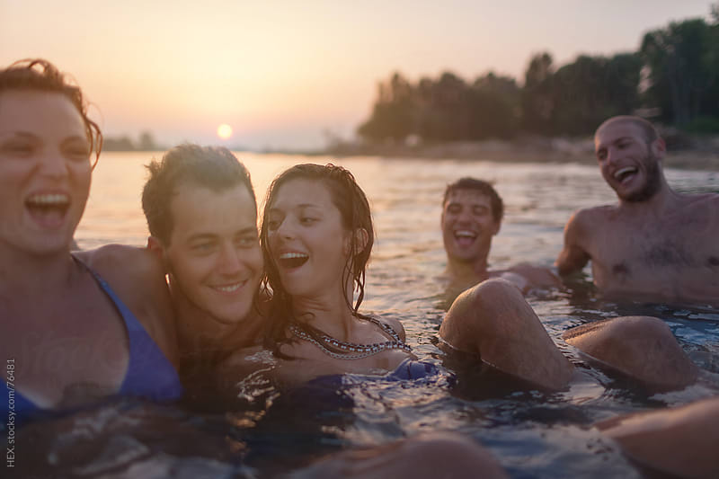 Friends Swimming During Sunset by HEX . for Stocksy United