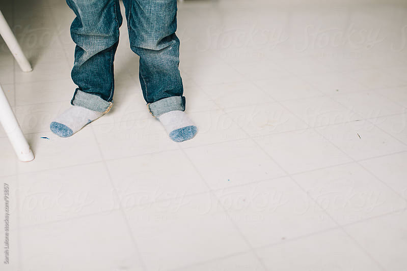 the socked feet of a little kid wearing jeans with a cuff by Sarah Lalone for Stocksy United
