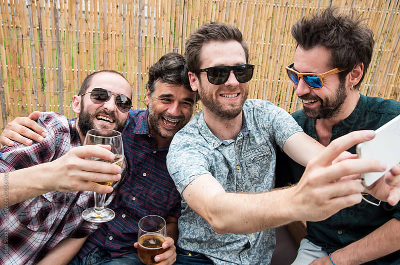 Group of men friends with sunglasses taking a selfie on a bar by Bisual Studio for Stocksy United