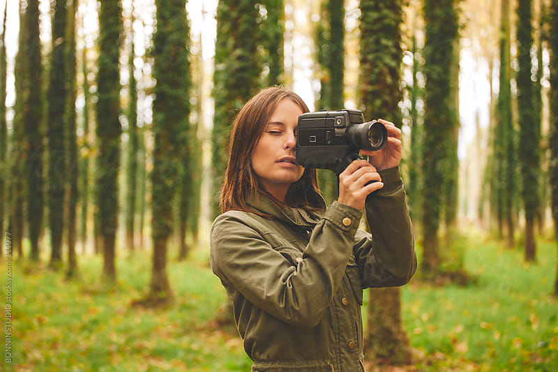 Woman standing with film camera an autumnal forest. by BONNINSTUDIO for Stocksy United