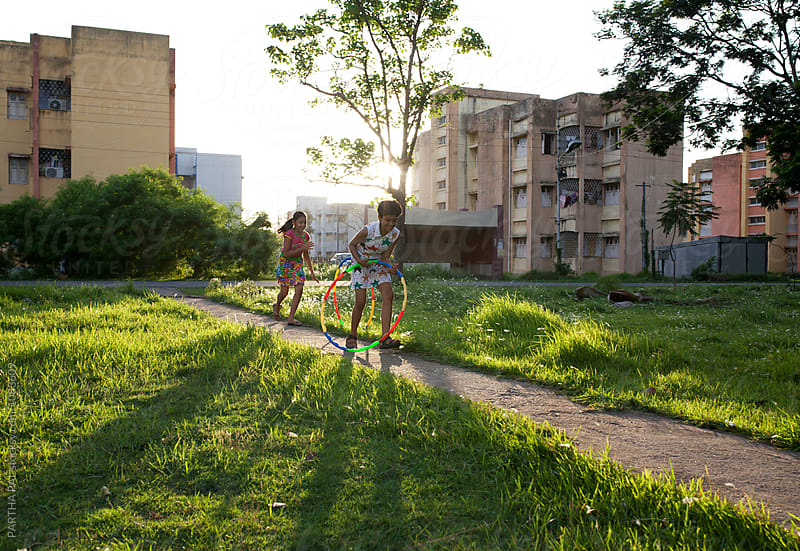 Two teenage girls playing and making fun with Hula Hoop by PARTHA PAL for Stocksy United