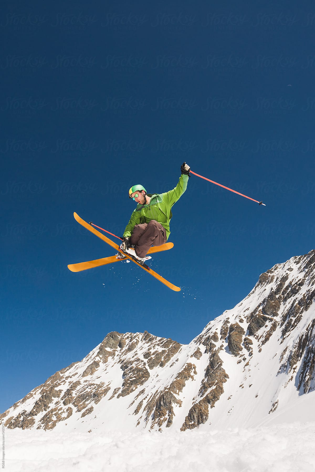 fe1bd60638b1 Male rider performing helicopter ski trick midair against the blue sky by  RG B Images for Stocksy