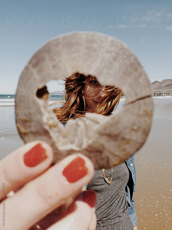 Woman Holding Sand Dollar Frame on the Beach by Kevin Russ for Stocksy United