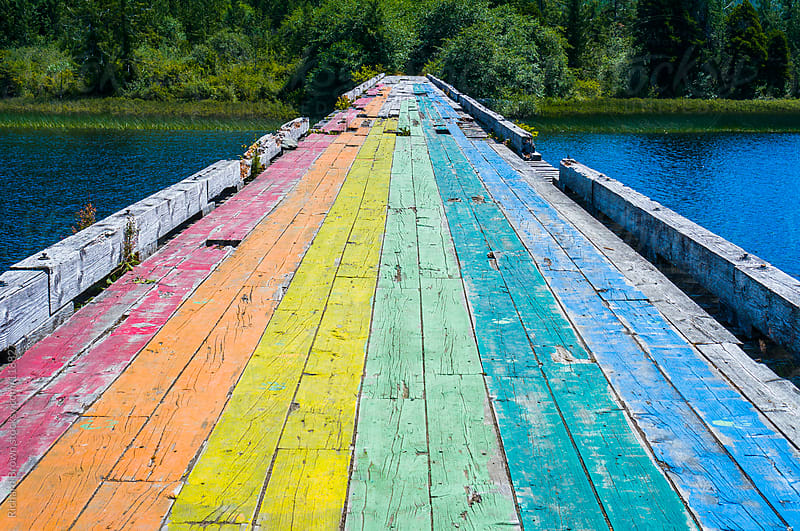 A rundown, rainbow painted bridge over a lake.  by Richard Brown for Stocksy United