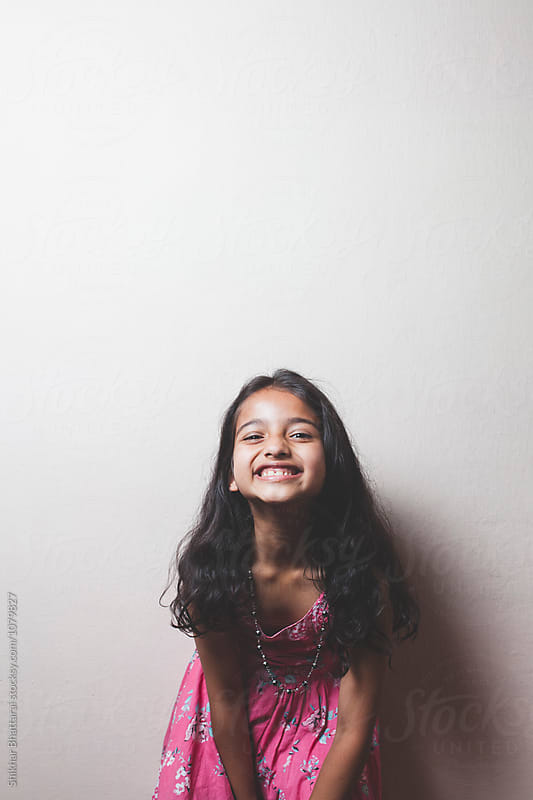 Young girl making faces, smiling for the camera. by Shikhar Bhattarai for Stocksy United