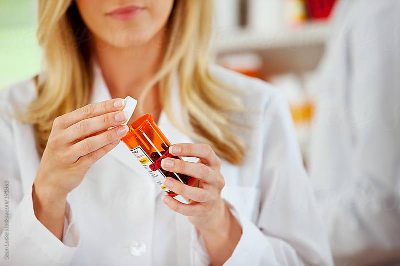 Pharmacy: Pharmacist Closing Medication Bottle by Sean Locke for Stocksy United