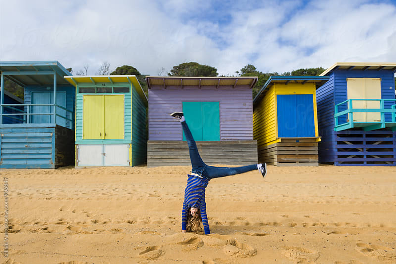 tween going doing a cartwheel at the beach in front of beach huts by Gillian Vann for Stocksy United