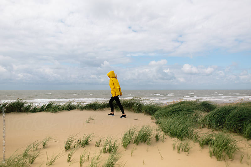 Woman walks up a dunes on a windy beach wearing a yellow raincoat by Denni Van Huis for Stocksy United