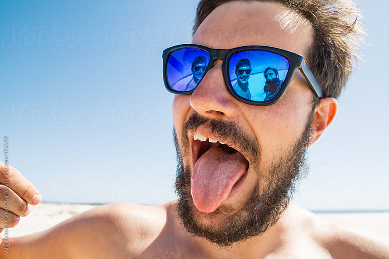Young hipster man sticking out tongue on the beach with his friends showing on the reflection of his sunglasses by Alejandro Moreno de Carlos for Stocksy United