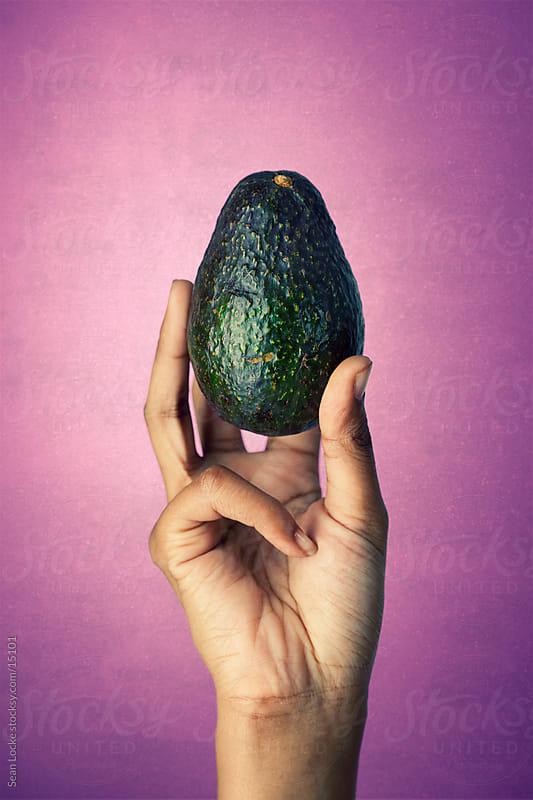 Healthy: Holding a Whole Avocado by Sean Locke for Stocksy United