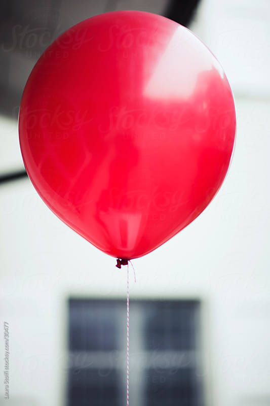 Red balloon in backyard by Laura Stolfi for Stocksy United