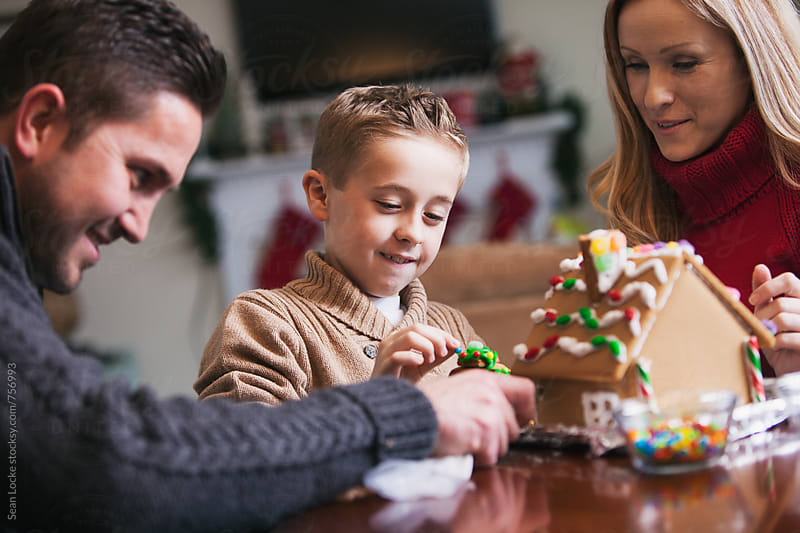 Christmas: Family Fun Time While Decorating Gingerbread House by Sean Locke for Stocksy United