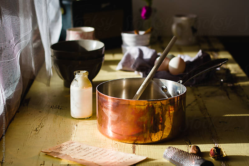 A kitchen scene where custard is being made. by Helen Rushbrook for Stocksy United