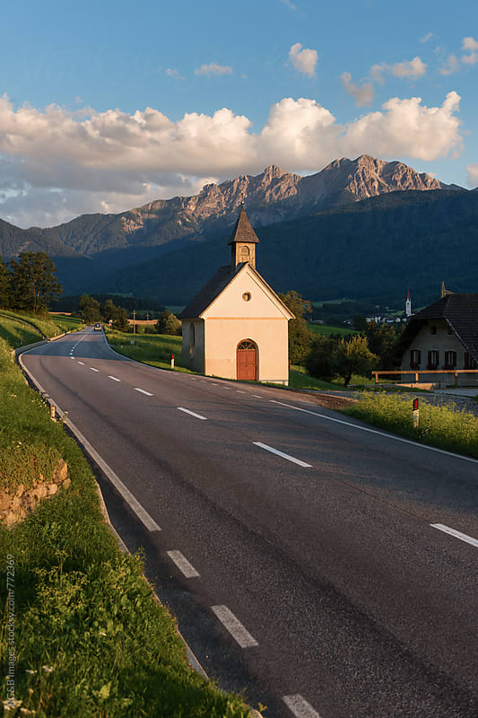 Road and old little chapel in the Alps at sunset by RG&B Images for Stocksy United
