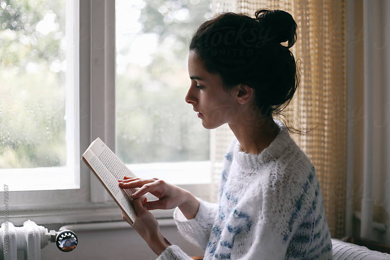 Beautiful woman reading a book near a window  by Marija Mandic for Stocksy United
