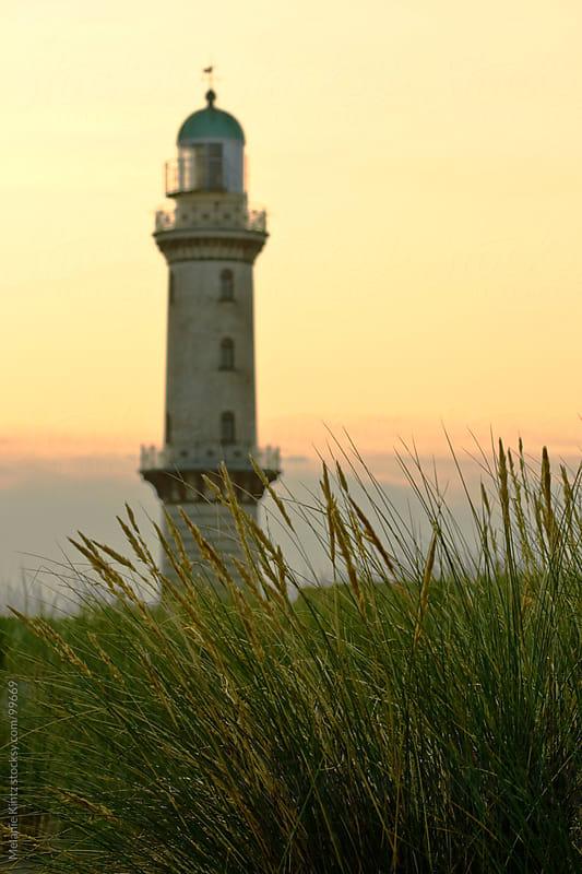 Lighthouse at sunrise behind dunes by Melanie Kintz for Stocksy United